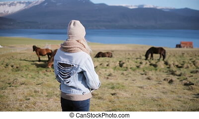 Back view of young stylish woman standing on the nature and...