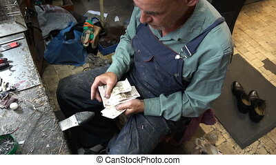 shoemaker counts the money earned at the end of the working day