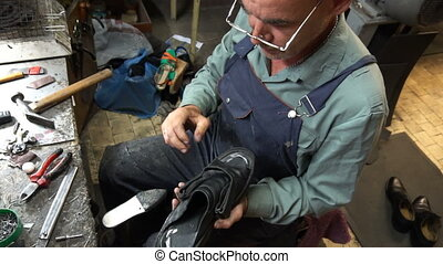 a shoemaker cleans in the workplace at the end of the day