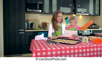 Emotional mother and daughter girl studying sweets recipes...