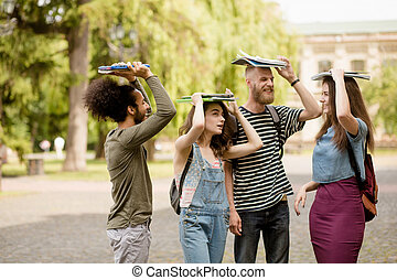 Young students fooling around in university campus. College...