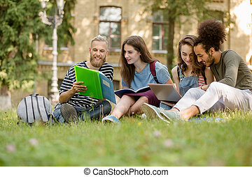 View on students sitting on lawn studying in college garden.