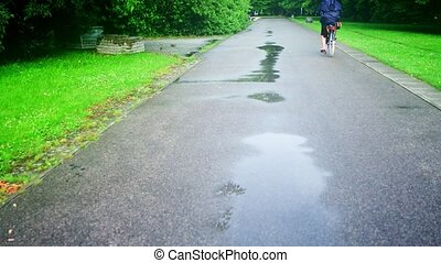 Unknown woman cycling along park road after summer rain -...