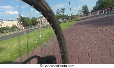 Time lapse of a spinning rear bicycle wheel, ride along city bike path
