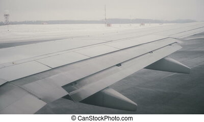View from the window on the wing of the airplane. The plane is riding on the runway, getting ready for departure.