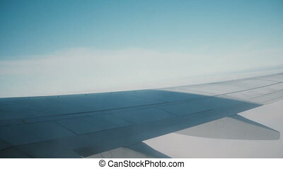 View from the window in the plane to sky and clouds. Traveling by air concept. Close-up view of wing of an airplane.