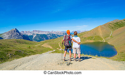 Couple of hiker on the mountain top looking at blue lake and mountain peaks. Summer adventures on the Alps. Wide angle view from above.
