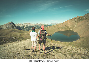 Couple of hiker on the mountain top looking at blue lake and mountain peaks. Summer adventures on the Alps. Wide angle view from above, toned image, vintage style.