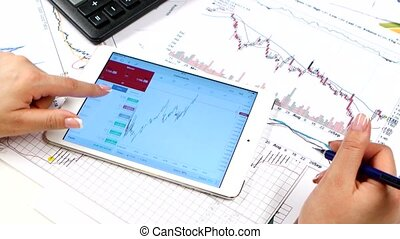 Hands of woman scans on tablet online stock market. Trading