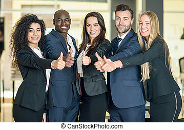 Group of businesspeople with thumbs up gesture in modern office.