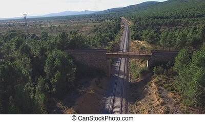 Mountain cyclist riding over bridge crossing track - Aerial...