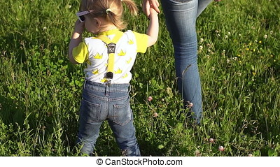 Mom and daughter are walking in the park. Family outdoors on a sunny day. Children with mother outdoors in summer. A woman with little girl is walking along the green grass.