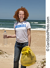 Volunteer collecting garbage on beach - Young female...