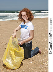 Beach clean up: Volunteer collecting waste - Young female...