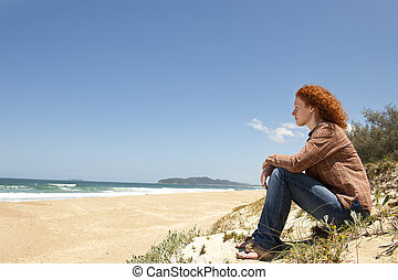 pensive woman sitting on the dunes watching the sea