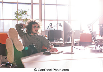 businessman sitting with legs on desk - Full length of a...