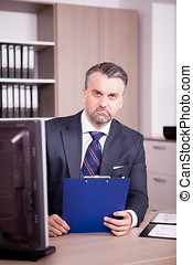 Businessman at his desk in office looking at a folder