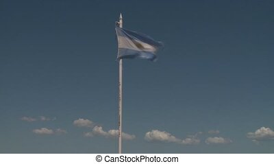 Argentinian flag waving in wind against blue sky