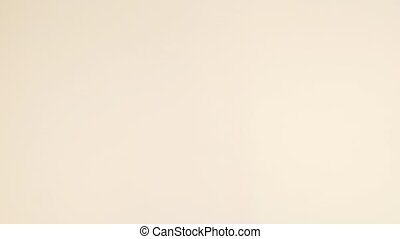 Small Book On Beige Background - Small orange book with a...