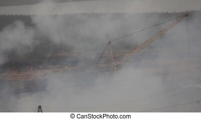 Smoke from factory chimney and tall crane in background -...