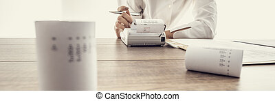 Low angle wide view of a woman doing calculations on an...
