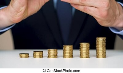 Man stacking gold coins into increasing columns - Savings,...