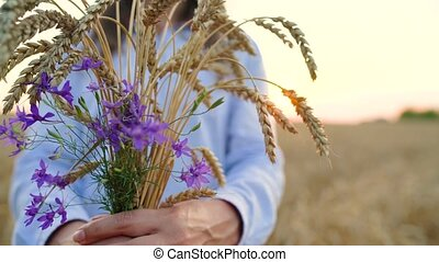 Woman holding a bunch of wheat ears and field flowers on the field