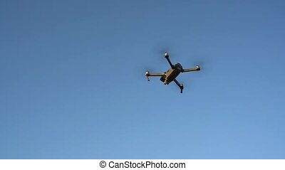 Small quadrocopter flying against the sky - Grey...