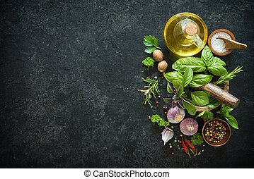 Herbs and spices on black stone table. Ingredients for...