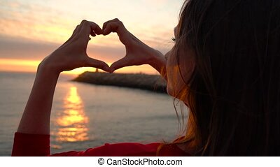 Woman making heart symbol with her hands during sunset on...