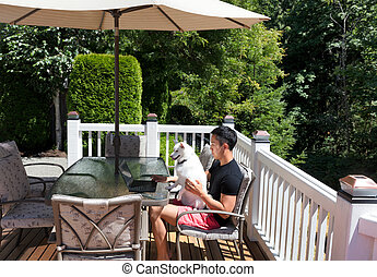 Young man and his pet dog working from home on his cedar home deck