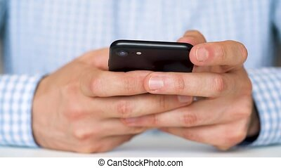 Businessman using smartphone for text messaging close up