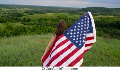 Woman waving a US flag is standing on top of a hill - the...