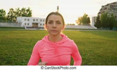 Woman runs through the stadium at sunset - Young woman runs...