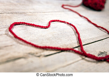 red woollen ball and string on wooden background, symbol Heart