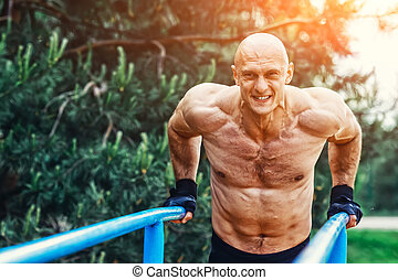 Bald Man doing push ups on parallel bars in a park - Man...