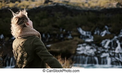 Freedom: young woman standing near the Barnafoss waterfall in Iceland and enjoying the view. Girl raises hands and jumps