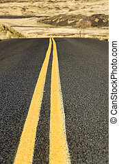 Double yellow lines on paved road in rural desert area