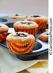 Muffins with berries on a yellow napkin and a wooden board