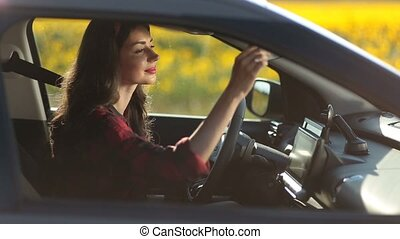 Pretty young woman driving car on summer road trip -...