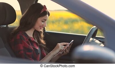 Charming woman using smartphone while driving car