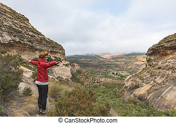 Tourist standing with outstretched arms and looking at the panoramic view in the majestic Golden Gate Highlands National Park, travel destination in South Africa. Concept of adventure and traveling people.