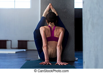 Back view of muscular young woman doing advanced stretching...