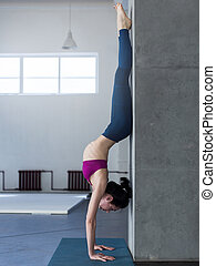 Yoga girl doing handstand with backbend exercise in gym.