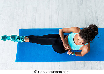 Top view of young fit woman working-out doing bicycle...
