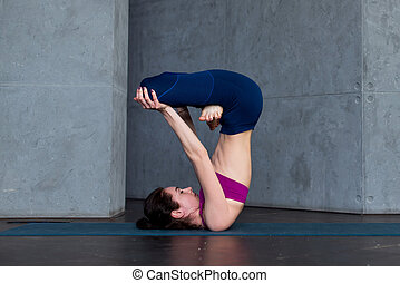 Advanced young yogini practicing Hatha yoga standing in...