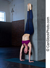Slender young woman standing in inverted yoga pose...