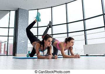 Two sportive girlfriends doing butt toning exercise performing donkey kicks on a mat in light modern fitness hall with big windows.