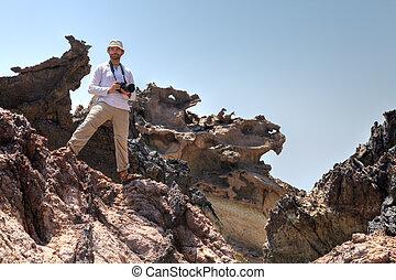 Photographer traveler stands on rock in Hormoz Island,...