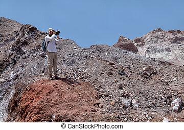 Photographer takes a photo in deserted area Hormuz Island,...
